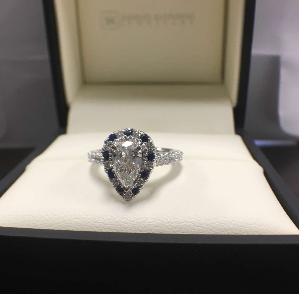 Pear shape diamond halo engagement ring with blue sapphires